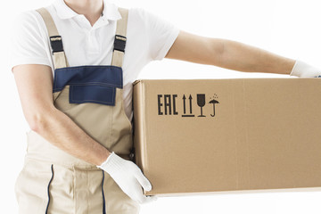 Mover holding in hands cardboard box isolated on white background. Relocation services concept. Loader in uniform with box. Worker in gloves with box for moving.