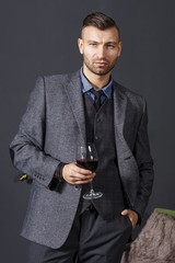 Portrait of elegant confident handsome man in business suit with glass of red wine on gray wall background. Rich fashionable young man with wine. Fashion model seriously looking.