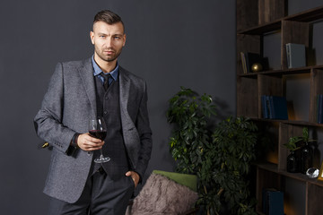 Portrait of elegant confident handsome man in business suit with glass of red wine in luxurious interior. Rich fashionable man with wine in room luxury apartment. Fashion model seriously looking.