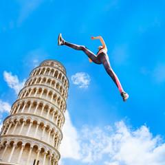 Sporty girl jumping near Pisa Tower