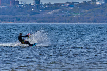 A male kiteboarder rides on a board on a large river. He performs various exercises while moving on water. Splashes of water scatter in different directions. The sun's rays shine in the water.