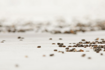 selective focus of chia seeds on white wooden tabletop