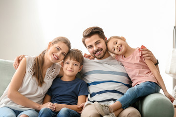 Portrait of couple with children on sofa at home. Happy family