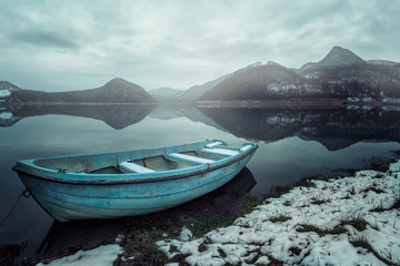 Misty morning / Frosty winter view of a boat at a lake coast