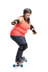 Overweight woman wearing protective gear riding a longboard