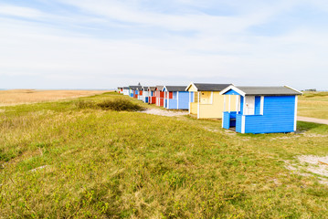 Skanor, Sweden - Long row of colorful bathing sheds along the coast.