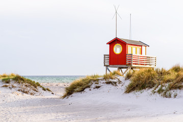 Skanor, Sweden - Red and yellow lifeguard cabin on stilts overlooking the sandy beach. Sunny coastal evening with sunshine and a little haze.