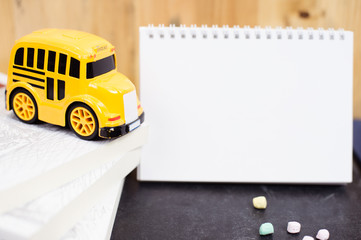 Back to school concept with school bus toy, books and blank note book.