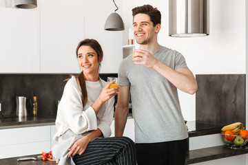 Portrait of a happy young couple drinking orange juice