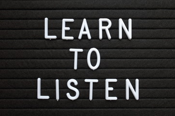 The words Learn To Listen in white plastic letters on a black letter board as a reminder for when dealing with people or improving your knowledge