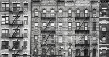 Black and white picture of old buildings with fire escapes, one of the New York City symbols, USA.