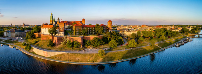 Krakow, Poland. Wide aerial panorama at sunset with Royal Wawel castle and cathedral. Far view of  old city and old Jewish Kazimierz district. Vistula river bank, park, promenade and walking people
