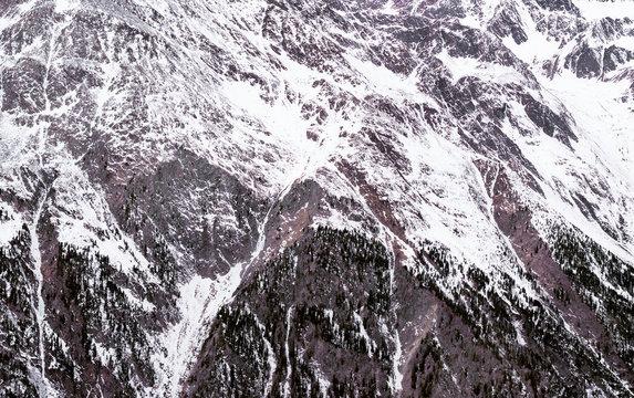 Winter Alpine background. The mountainous terrain in the snow