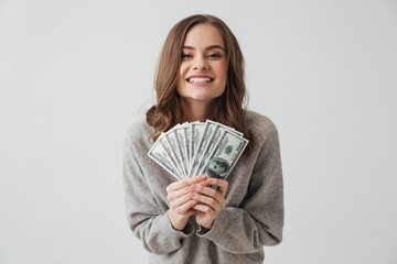 Cheerful brunette woman in sweater holding money and rejoices
