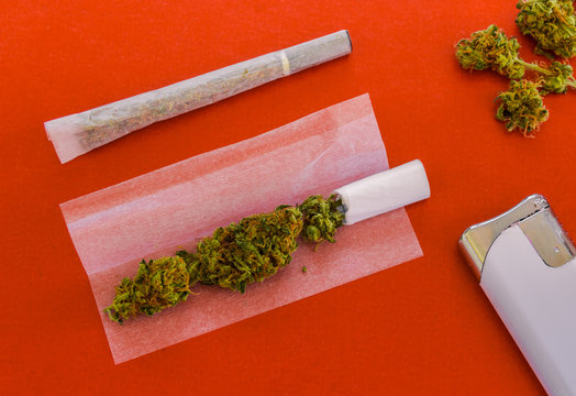 Rolling a joint of marijuana. Views of two joints, one prepared to roll, lighter and marijuana buds isolated on red background.
