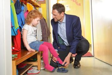 Vater Papa holt Kind Tochter aus Kindergarten