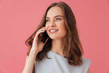 Smiling young woman talking by phone.