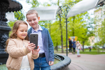 Two little kids taking selfie outdoor. Love friendship fun concept. Small adults