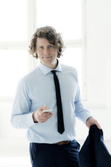 Smart businessman standing in office, using mobile phone