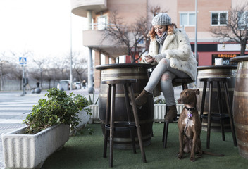 Woman in bar terrace with her dog looking smartphone and smiling in outdoors image.