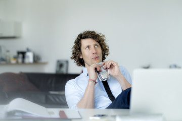 Easygoing businessman sitting in office, drinking juice