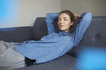 Portrait of woman wearing denim shirt relaxing on the couch