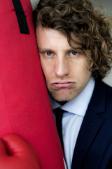Disappointed businessman leaning on punch bag