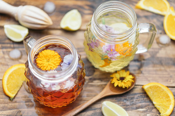 Refreshing mineral water with edible flowers, Viola wittrockiana, Dianthus caryophyllus, Calendula officinalis, lemon and orange