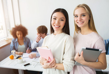 A picture of two beautiful asian girls standing and smiling. Brunette holds a pink notebook while the blonde girl has a tablet in her hands. There their frinds sitting behind them and studying.