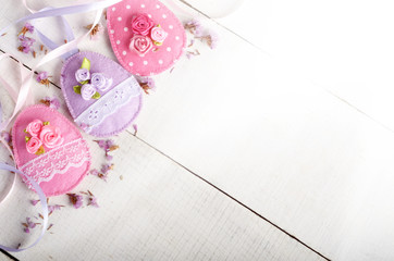 Handmade patchwork pink and lilac felt easter eggs on white wooden table