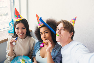 Guy is taking a selfie with his two friends. They are celebrating afro american girls birthday. People wears birthday hats. Also girls have whisltes.