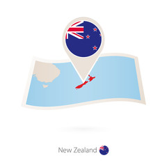 Folded paper map of New Zealand with flag pin of New Zealand.