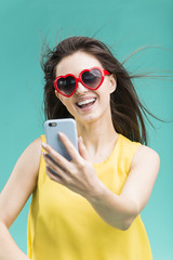 Beautiful smiling brunette girl wears yellow t-shirt and sunglasses making selfie by smartphone before blue background