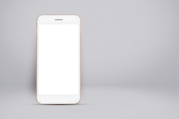 Smart phone on gray gradient wall background.