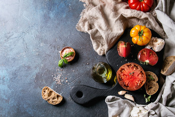 Variety of red and yellow organic tomatoes with olive oil, garlic, salt and bread for salad or bruschetta on wooden cutting board with linen cloth over blue texture background. Top view, space.
