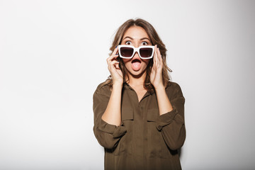 Portrait of a shocked young woman looking over sunglasses