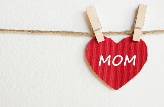 Happy mother's day greeting card, Love mom word on red fabric heart shape hanging over white background with copy space for text