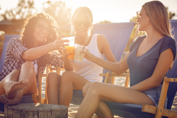Group of young casual female friends sitting on beach on sun beds,hangout and relaxing.
