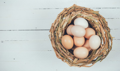 eggs from domestic chickens in wicker basket on white wooden background with copy space