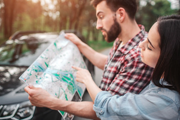 Young and attractive tourists are studying map. Guy is holding it while girl is pointing in one place on map. They made a stop in forest and standing outside on the road.