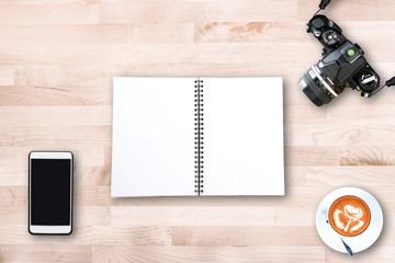Top view of modern office workplace with vintage film camera , smart phone , notebook paper , latte art coffee cup on wooden table background.