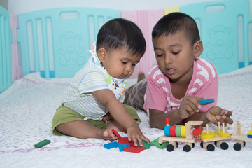 Two brother play wooden toy in room