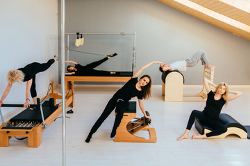 Group of fшму people doing pilates exercises with chair, barrel, spine corrector, reformer, cadillac - different equipment in modern eco studio interior.