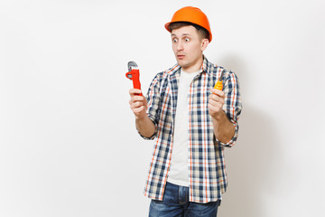 Young shocked handsome man in protective orange hardhat holding toy screwdriver and adjustable wrench isolated on white background. Instruments for renovation apartment room. Repair home concept.