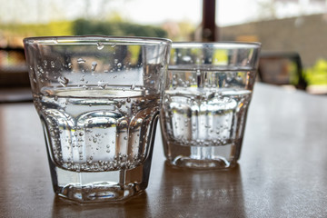 Two freshly poured glasses of sparkling water on wood table.