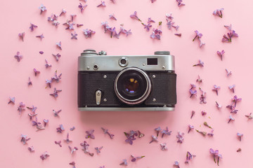 stylish old photo camera on pink background with lilac flowers. creative travel trendy flat lay with space for text. modern fashion and hipster image. summer vacation concept