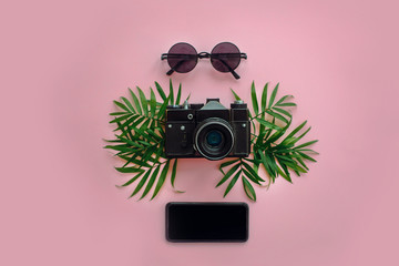 stylish black photo camera with green palm leaves, sunglasses and phone on trendy pink background, flat lay. modern hipster travel  image. summer vacation,space for text