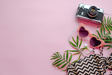 summer vacation concept. stylish pink sunglasses, modern swimsuit, photo camera,headphones  and green palm leaves on pink background, flat lay. space for text.   time to travel