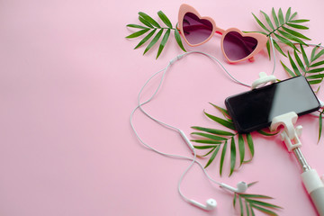summer vacation concept. stylish pink sunglasses, phone on selfie stick, headphones, and green palm leaves on pink background, flat lay.  space for text. time to travel