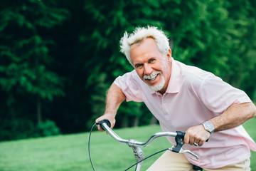 lively older man riding his bicycle, laughs and enjoys life. Senior man on bike, having fun